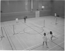 Shows three women and one man playing doubles game of badminton on indoor court, Waltham Abbey
