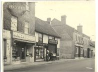 Row of shopfronts at north east end of Sun Street, Waltham Abbey: including Scotts, family bakers No. 42, Devon Library, stationer and lending library, No. 44, J.W Blake and Son, commercial vehicle builders and No. 44, and the Angel public house, No. 48