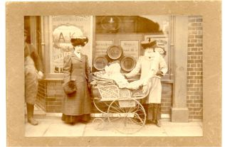 Two women posing with baby in pram outside MacMullen's off-licence on Sun Street - this shop later became Mr Fiddler's Greengrocer
