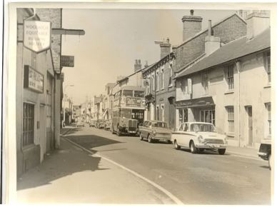 Row of buildings in Sun Street, Waltham Abbey : cars on road, and No. 242 bus to Upshire